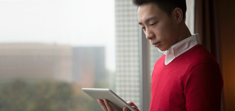 student wearing a red jumper using a tablet device